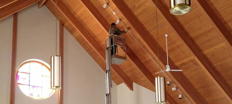 Todavich Electric employee working on lights in church